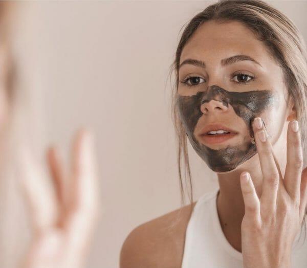 Woman applying Nordic Mud Peat Mask